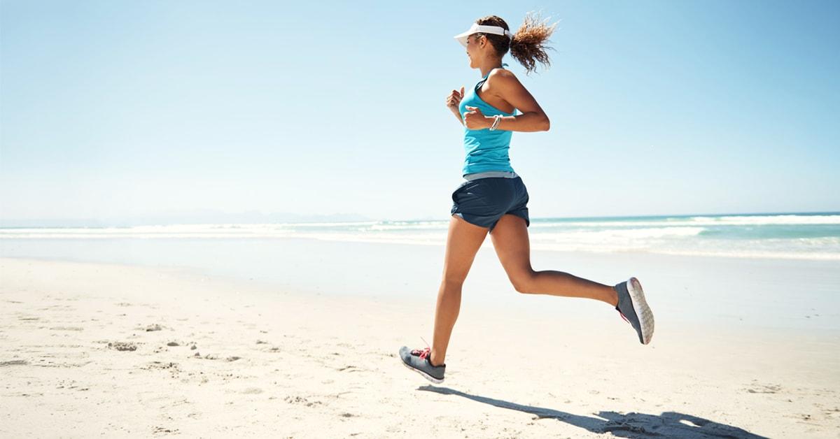 Ragazza con scarpe per correre sulla sabbia al mare