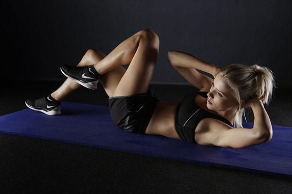 Ragazza con scarpe da ginnastica esegue esercizi su tappetino in palestra
